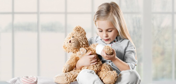 Blond girl blowing on LIVOPAN bear's arm.  Only to be used for LIVOPAN paediatrics. Campaign idea: Connects to breathing – in and out. The visuals show people inhaling and exhaling to capture the idea that pain relief is just a few breaths away.