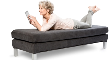 Lady is lying on couch, checking the webshop on her tablet. This image is used as keyvisual for the Homecare Benelux webshop.